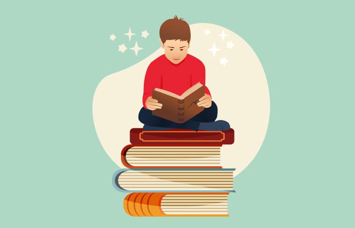 積み重なった本の上で読書する少年
