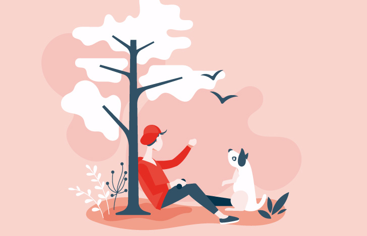 木の根元でくつろぐ少年と犬