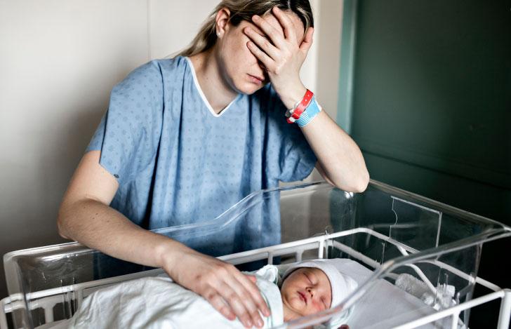 新生児ベッドの横で辛そうに手で顔を覆う女性