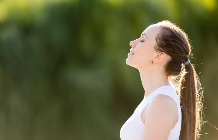 自然の中で深呼吸する女性の横顔