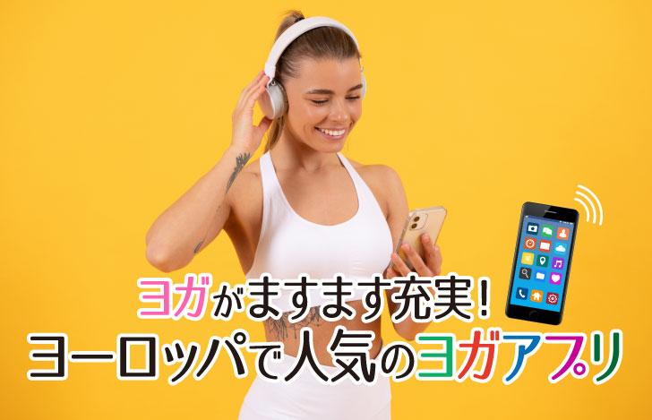 ヘッドフォンとフィットネスウェアを身につけスマホアプリを見る女性