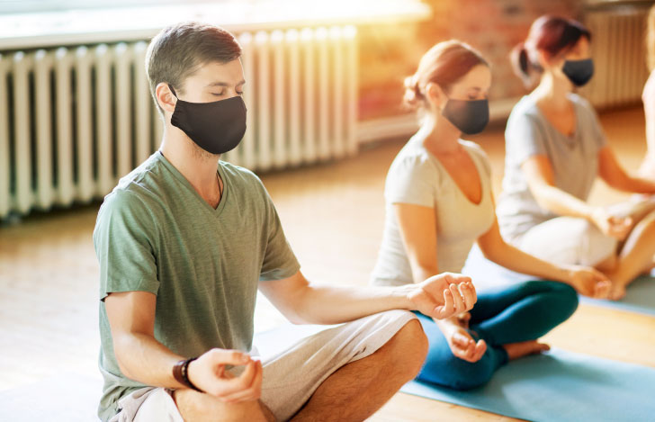マスクをして安楽座で座るヨガの練習生たち