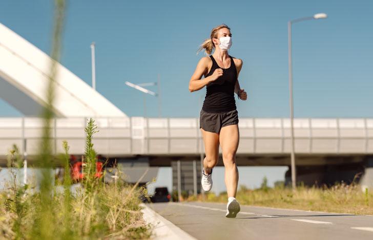 マスクをつけて外を走るランニングウェアの女性