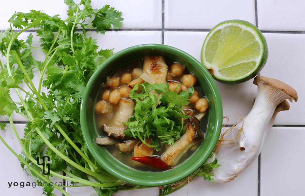 緑のお皿に盛り付けたヒヨコ豆とエリンギの酸っぱスパイシースープ