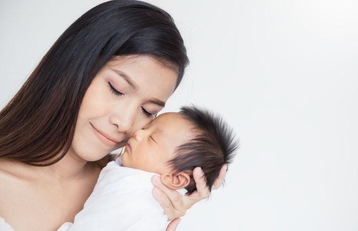 生まれたばかりの赤ちゃんに頬擦りをする母親