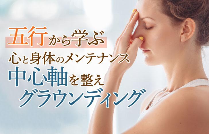 眉間に指をあて目を閉じる女性の横顔