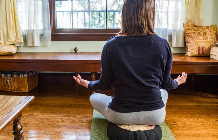 ヨガマットの上のクッションに座って瞑想する女性