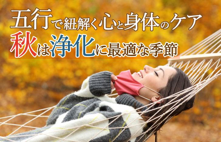 紅葉の木々の中でハンモックに横たわり口元からマスクを外す女性